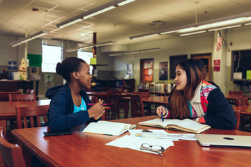 Refugee high school students talking at table, USA