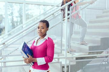 Portrait of teenage girl standing against staircase in high school