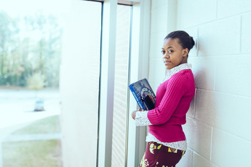 Portrait of teenage girl with books leaning on wall