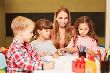 Erzieherin und Kinder im Kunstunterricht