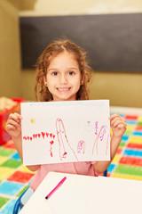 Mädchen zeigt stolz ein Bild im Malkurs