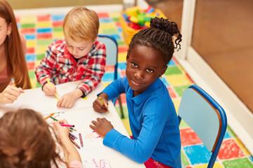 Afrikanisches Mädchen und andere Kinder malen