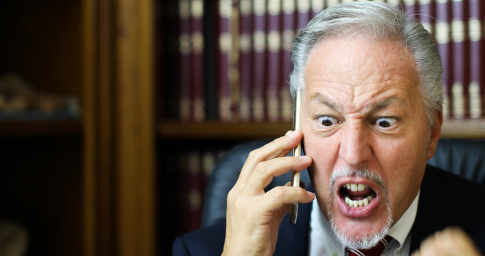 Very angry lawyer talking on the phone in his studio