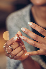 Close up of woman putting ring on finger