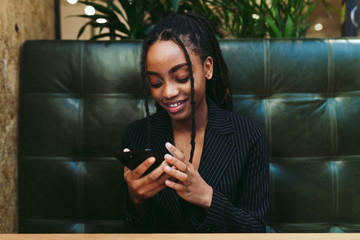 Smiling young businesswoman using smartphone in the office