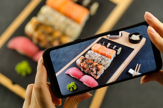 Young woman taking photo of sushi plate on smartphone. Taking food photo with mobile phone.