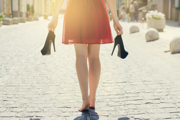 Elegant girl in red dress with high-heels in hands, walking street barefoot. Close up cropped rear behind back view photo. Sun beam light rays shine sunburst burst  shiny flare effect glare sparkle