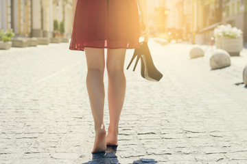 Woman in dress, high heel shoes hand, walking in city barefoot. Close up cropped rear behind back view photo of woman's legs. Sun beam light rays shine sunburst burst  shiny flare effect glare sparkle