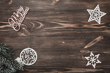 View from above of a Merry Christmas inscription and handmade tree toys on wooden background, greeting card with space for text writing