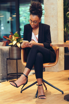 Young businesswoman using smartphone while sitting on chair