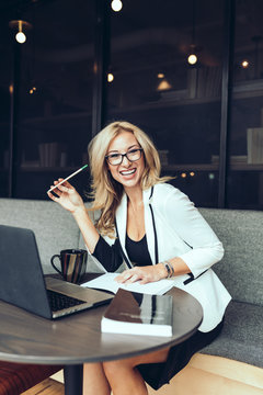 Smiling businesswoman sitting on sofa in office