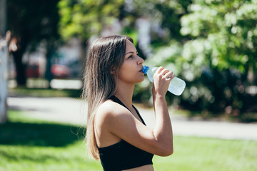Portrait of fit and sporty young woman drinking water