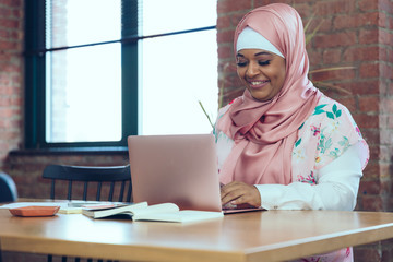 Smiling Businesswoman working on laptop while sitting in office