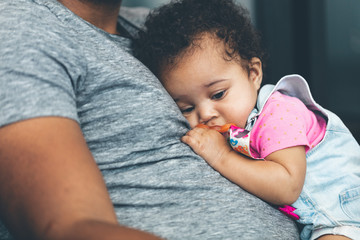Daughter lying on father's stomach