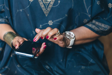Mid section of woman using smartphone