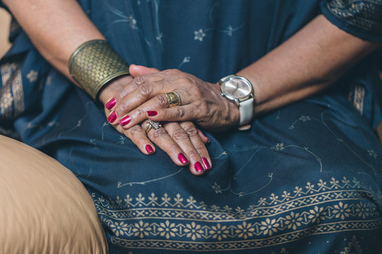 Mid section of woman hands resting on lap