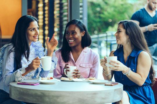 Smiling female friends having coffee in coffee shop