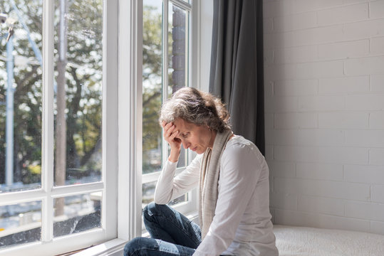 Waist up view of middle aged woman sitting by window resting head on her hand (selective focus)