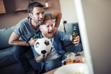 Friends enjoy the football game on TV
