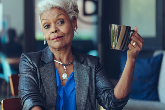Elegant senior woman sitting at cafe table with cup