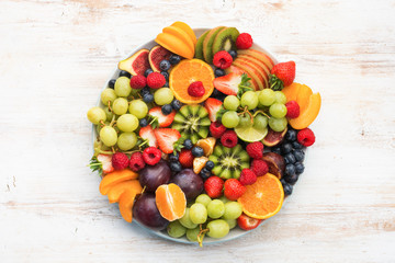 Healthy fruit platter, strawberries raspberries oranges plums apples kiwis grapes blueberries on the white wooden table, top view, copy space for text, selective focus