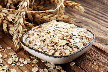 Oatmeal and oatmeal on the wooden background. Healthy eating concept