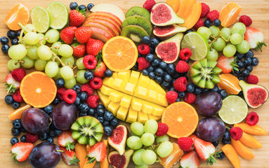 Wall Mural - Healthy raw fruits and berries platter background, strawberries raspberries oranges plums apples kiwis grapes blueberries, mango on the serving board, top view, selective focus