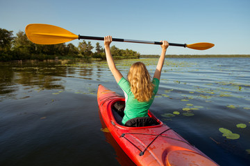 Woman in a kayak on a river with a raised oar