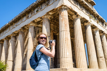 Young woman takes a picture of Temple of Hephaestus in Agora, Athens