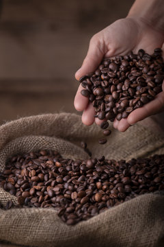 Crop close-up view of sack of fresh coffee beans with hands