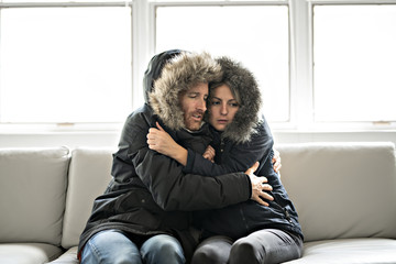 Obraz Couple have cold on the sofa at home with winter coat - fototapety do salonu