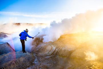 Homme prenant un selfie avec paysage geyser au lever du soleil en Bolivie
