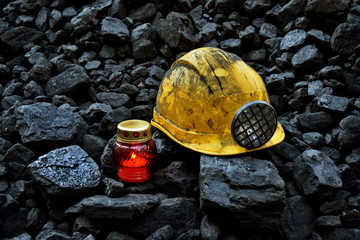 Vigil light, candle with mining helmet on cheap of coal