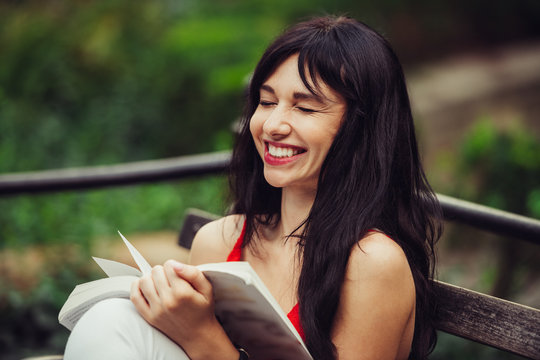 Beautiful smart woman reading a book and laughing in the green park outdoors