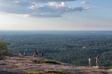 Several unidentifiable people looking out over the green trees and forests visible from the top of Stone Mountain in Georgia on a lovely summer day