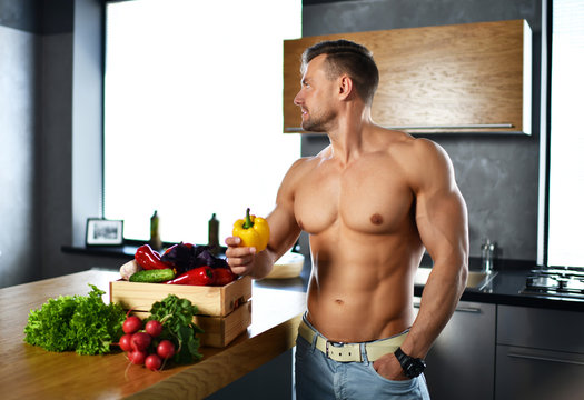 muscular sport man standing on kitchen with groceries vegetables hold yellow pepper in hands looking at the corner smiling