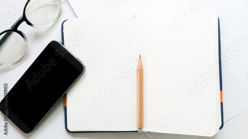 Wall mural office desk table with smart phone and notebook on white background