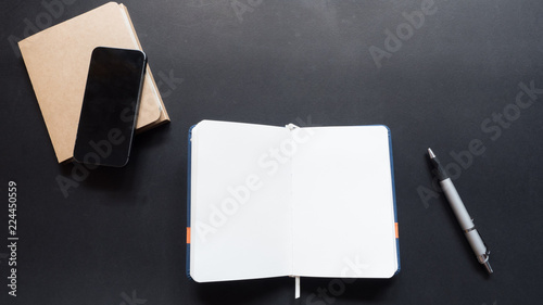 Wall mural workspace desk copy space top view with notebook  black background