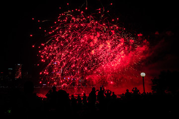 Beautiful red fireworks with people background at night