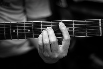 Guitarist playing the guitar, fingles press cord on the fretboard