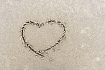 Symbol of heart written by hand on sand of beach with copy space