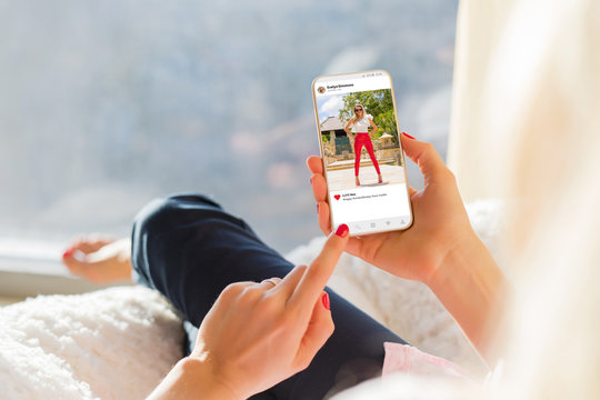 Woman looking at photo sharing app on mobile phone