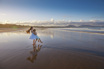 Happy little girls on a beach, kids and sunset