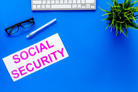 Social security concept. Printed words social security on blue office desk background with computer keyboard top view copy space
