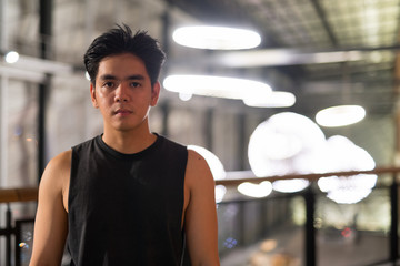 Young handsome Asian man in the city outdoors at night