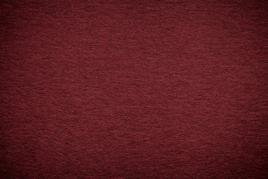 Texture of old dark red paper background, closeup. Structure of dense maroon cardboard
