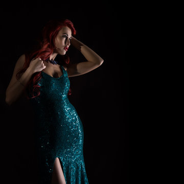 Young redhead sexy woman in blue elegant dress poses in a dark. free space for your text