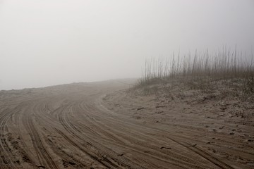 Amelia Island, Florida, USA: Tire tracks in the sand at mist-covered American Beach, on the Atlantic Ocean.