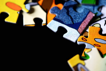 Children's puzzles scattered on a dark background close up