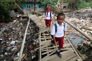 Students cross a bamboo bridge above a garbage-filled stream branching off the Ciliwung River in Bogor